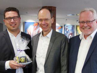 Bildunterschrift:Landrat Dr. Michael Lübbersmann (Mitte) und Geschäftsbereichsleiter Siegfried Averhage (rechts) gratulieren dem neuen MaßArbeit-Vorstand Lars Hellmers. Mit ins Vorstandsbüro zieht auch die neue BVB-Tasse des bekennenden Dortmund-Fans ein.Foto: Landkreis Osnabrück /Eckhard Wiebrock